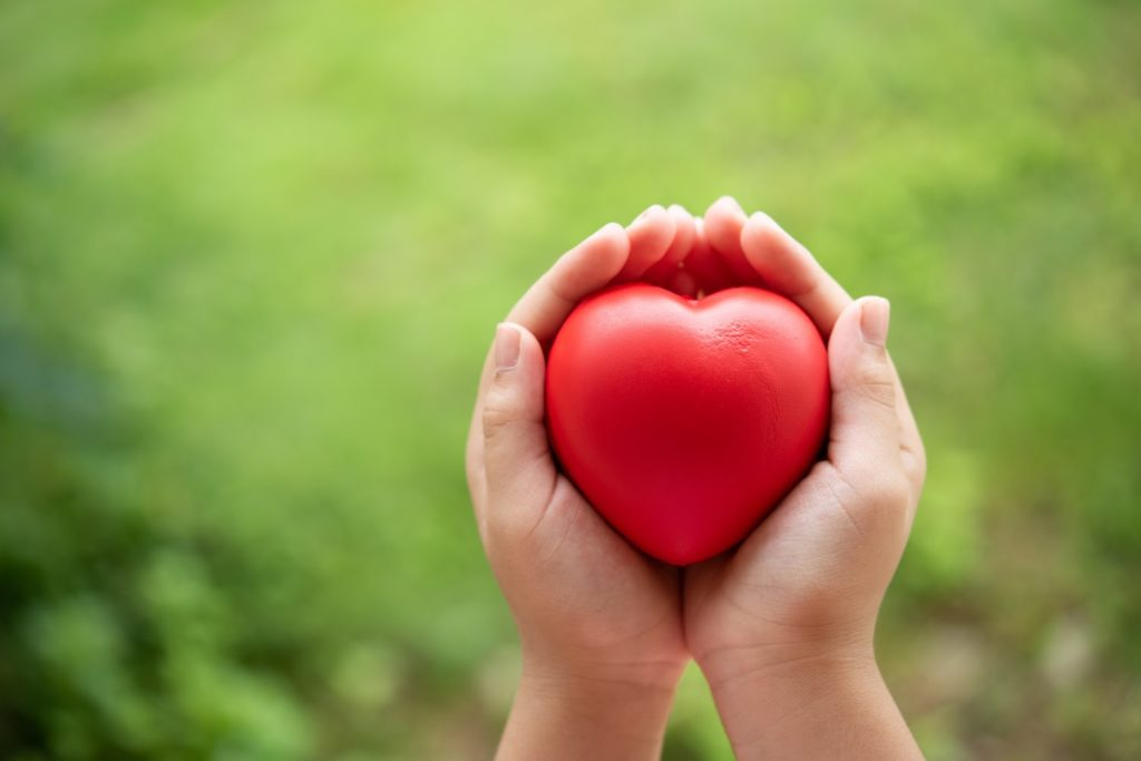 child-holding-red-rubber-heart